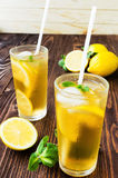 Two glasses of ice tea with ice-cubes on wooden table Royalty Free Stock Images