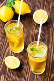 Two glasses of ice tea with ice-cubes on wooden table Stock Photos