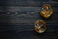 Two glasses with ice and whiskey on wooden background . Royalty Free Stock Photo