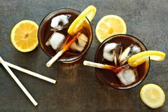 Two glasses of iced tea, downward view on stone background. Two glasses of cold iced tea with lemon slices and straws, downward view on dark stone background royalty free stock photography