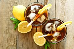 Two glasses of iced tea, overhead view on wood. Two glasses of iced tea with lemon, overhead view on a rustic wooden background royalty free stock photos