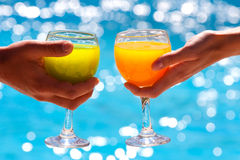 Two glasses with juice against blue water Royalty Free Stock Photo