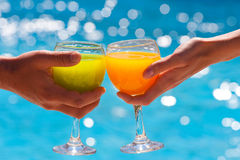 Two glasses with juice against blue water Stock Image