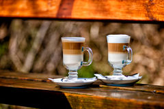 Two glasses of latte coffee beans. And spoon on old wooden bench stock image