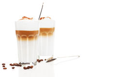 Two glasses latte macchiato with coffee beans and chocolate powder Royalty Free Stock Image