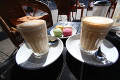 Two glasses of latte macchiato with macaron french dessert Royalty Free Stock Photography