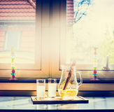 Two glasses of lemonade and jug on the kitchen table, retro toned. Stock Images