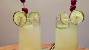Two glasses of lemonade with lime and raspberry, rotating.  stock footage