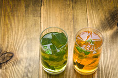 Two glasses of lemonade on a wooden background. Two cocktails with ice and mint Stock Photo