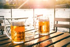 Two glasses of light beer with foam on a wooden table.On a boat. Garden party. Natural background. Alcohol. Draft beer. Landscape,. Golden stock image