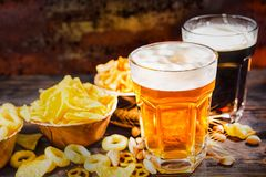 Two glasses with light and dark beer with great head of foam near plates with chips and scattered snacks on dark wooden desk. Food and beverages concept royalty free stock images