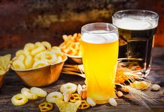 Two glasses with light unfiltered and dark beer near plates with Stock Photo