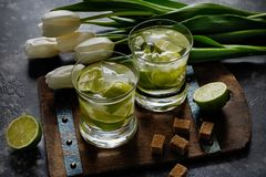 Two glasses with lime caipirinha with crushed ice against tulips. Stock Image