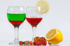 Two glasses of liquor, lemon and berries. The two glasses of transparent red and green liquor, lemon and berries Royalty Free Stock Photography
