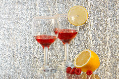 The two glasses of liquor, lemon and raspberries. The two glasses of transparent red liquor, lemon and raspberries Stock Photos