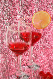 Two glasses liquor, lemon and raspberries. The two glasses of transparent red liquor, lemon and raspberries Stock Photography