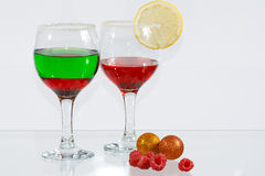 Two glasses of liquor, lemon and raspberries. The two glasses of transparent red and green liquor, lemon and raspberries Royalty Free Stock Images