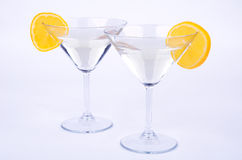 Two glasses of martini and lemon on blue. Two glasses of martini and slice of yellow lemon on a light blue background. glasses are highlighted in blue Stock Images