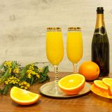Two glasses of mimosa cocktail, a bottle of champagne, fresh oranges, mimosa sprig on a wooden table stock photo