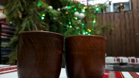 Two glasses of mulled wine on the background of Christmas garland and colorful lights. Concept of a happy winter holiday or new ye. Concept of a happy winter stock video footage