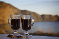 Two glasses of mulled wine. On a background of sea and rocks Stock Photos
