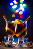Two glasses of mulled wine on bokeh background. Glasses with hot wine and spices on dark background with lights Royalty Free Stock Photo