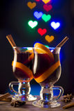 Two glasses of mulled wine on bokeh hearts background. Glasses with mulled wine on dark background with light hearts Stock Photo