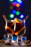 Two glasses of mulled wine on bokeh snow flake background. Glasses with mulled wine on dark background with light snow flakes Royalty Free Stock Photography