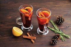 Two glasses of mulled wine with cinnamon, oranges, fir cones and rosemary on a brown background royalty free stock photo