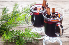 Two glasses of mulled wine with fir branch. Two glasses of mulled wine on the wooden background Stock Photos
