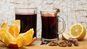 Two glasses of mulled wine, lemon , orange and nuts on wooden table Royalty Free Stock Image