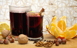 Two glasses of mulled wine, lemon , orange and nuts on wooden table Stock Image