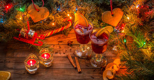 Two glasses of mulled wine with orange slices, candles and Christmas tree with garland and toys. On wooden background. Christmas time Royalty Free Stock Images