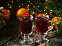 Two glasses with mulled wine on a wooden table with orange, cinnamon, cardamom, anise stars. Traditional winter hot stock photos