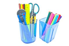 Two glasses with office supplies on white Stock Image