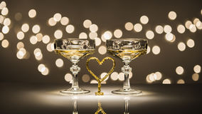 Two glasses one heart. Two glasses of sparkling wine one heart simbol in romantic atmosphere Stock Image