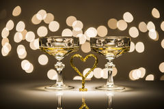 Two glasses one heart. Two glasses of sparkling wine and one heart simbol in romantic atmosphere Royalty Free Stock Image