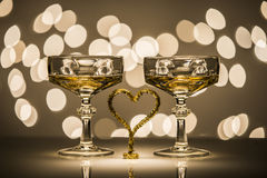 Two glasses one heart. Two glasses of sparkling wine and one heart simbol in romantic atmosphere Stock Photos