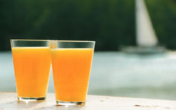 Two glasses of orange juice against sea. Two glasses of orange juice against small sailboat on sea Stock Photo