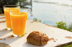Two glasses of orange juice and bread. On old white table Stock Photo