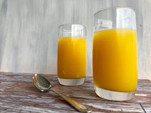 Two glasses of orange juice on the wooden bench with a silver spoon Royalty Free Stock Photo