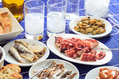 Two glasses of ouzo and appetizers Royalty Free Stock Photos