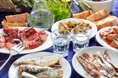 Two glasses of ouzo and appetizers Stock Images