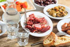 Two glasses of ouzo and appetizers Stock Photos