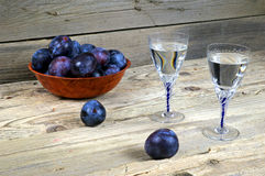 Two glasses of plum brandy with plums Stock Images