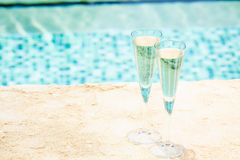 Two glasses of prosecco   at the edge of a resort pool. Concept Royalty Free Stock Images