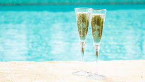 Two glasses of prosecco   at the edge of a resort pool. Concept. Of luxury vacation. Outdoor pool background. Horizontal, wide screen format Stock Images