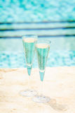 Two glasses of prosecco   at the edge of a resort pool. Concept Royalty Free Stock Image