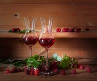 Two glasses of raspberry liqueur with ripe berries . Two glasses of raspberry liqueur with ripe berries on wooden background Stock Photos