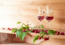 Two glasses of raspberry liqueur with ripe berries . Two glasses of raspberry liqueur with ripe berries on wooden background. Copy space for your text Stock Photography